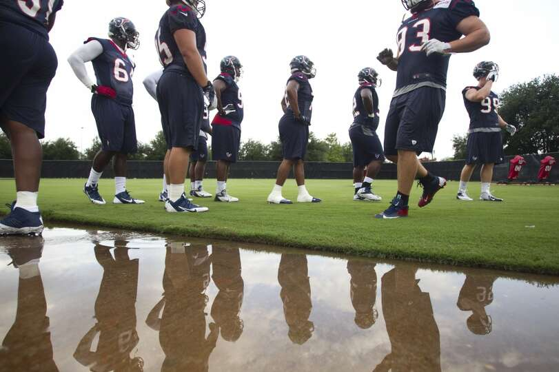 Texans defensive linemen are reflected in a puddle of water next to the practice field during the se