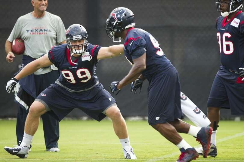 Texans defensive linemen Antonio Smith and J.J. Watt participate in drills during training camp.
