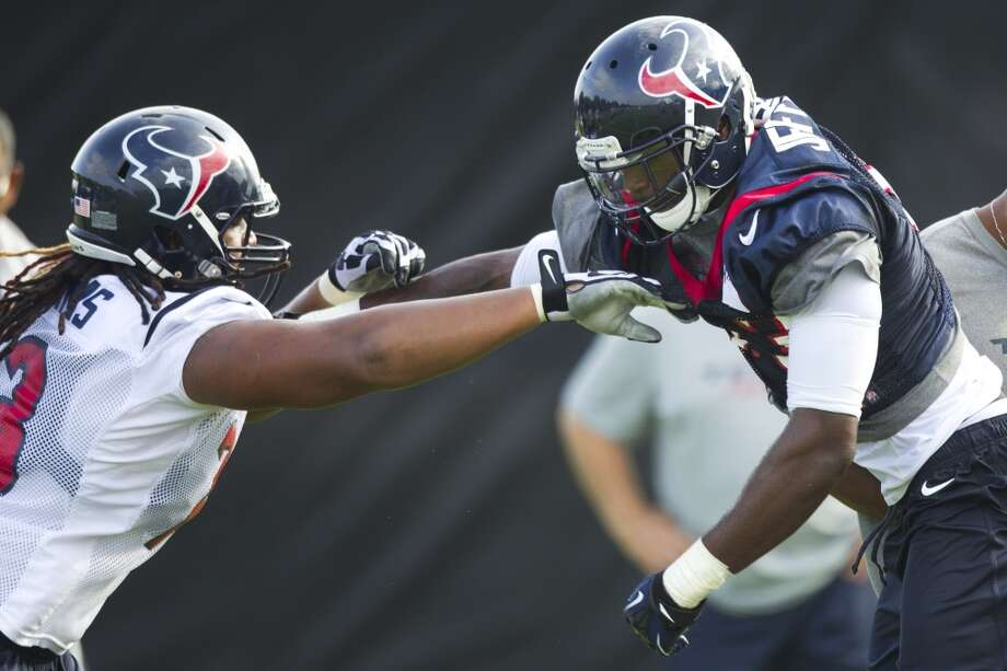 Texans linebacker Willie Jefferson and offensive lineman Brennan Williams get physical. Photo: Brett Coomer, Houston Chronicle