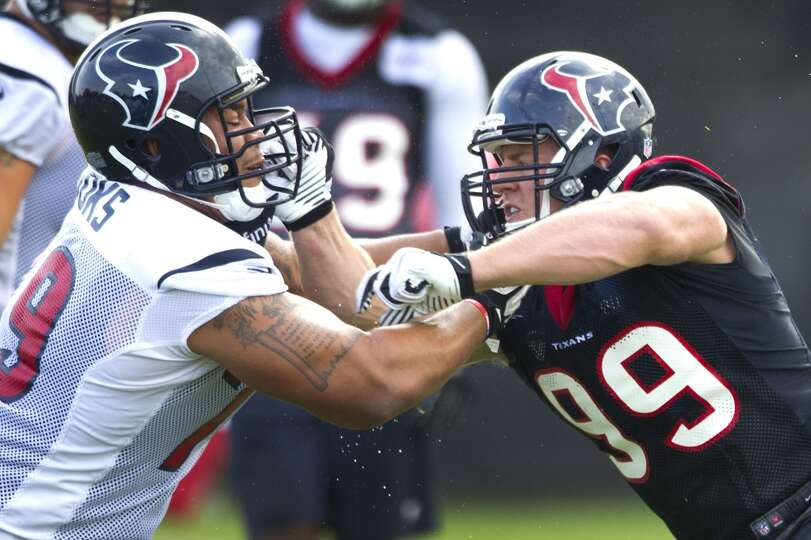 Texans offensive lineman Brandon Brooks gets tangled up with J.J. Watt.
