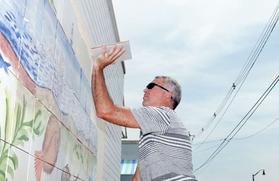Nicolas Martinez installs tiles to a 100 square foot mural at Calf Pasture Beach in Norwalk on Saturday, July 27, 2013. The tiles for the mural were created by artists Kim Salander and Georgette Wirth, of Wirth Salander Custom Tile. Photo: Amy Mortensen / Connecticut Post Freelance