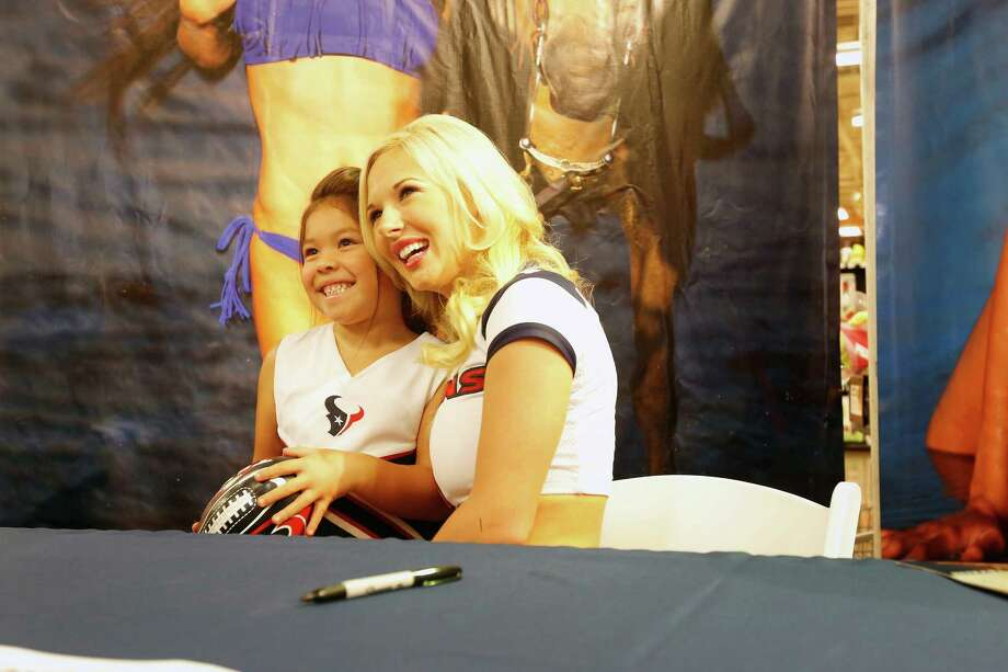 Texans cheerleader, Shelbie poses for a photo with 5-year-old Julia Moya, during an event unveiling the 2013-2014 Houston Texans cheerleader swimsuit calendar, Saturday, July 27, 2013 at the Kroger grocery store in the Heights neighborhood of Houston, Texas. (TODD SPOTH FOR THE CHRONICLE) Photo: © TODD SPOTH, 2013 / © TODD SPOTH, 2013
