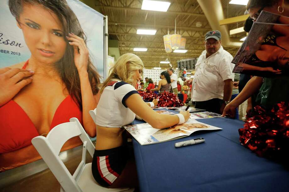 Texans cheerleader Kayla, signs a calendar for a fan, during an event unveiling the 2013-2014 Houston Texans cheerleader swimsuit calendar, Saturday, July 27, 2013 at the Kroger grocery store in the Heights neighborhood of Houston, Texas. (TODD SPOTH FOR THE CHRONICLE) Photo: © TODD SPOTH, 2013 / © TODD SPOTH, 2013