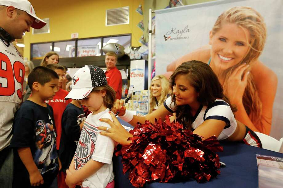 5-year-old Addison Harris, gets her Texans shirt signed by Texans cheerleader, Madison, during an event unveiling the 2013-2014 Houston Texans cheerleader swimsuit calendar, Saturday, July 27, 2013 at the Kroger grocery store in the Heights neighborhood of Houston, Texas. (TODD SPOTH FOR THE CHRONICLE) Photo: © TODD SPOTH,  2013 / © TODD SPOTH, 2013