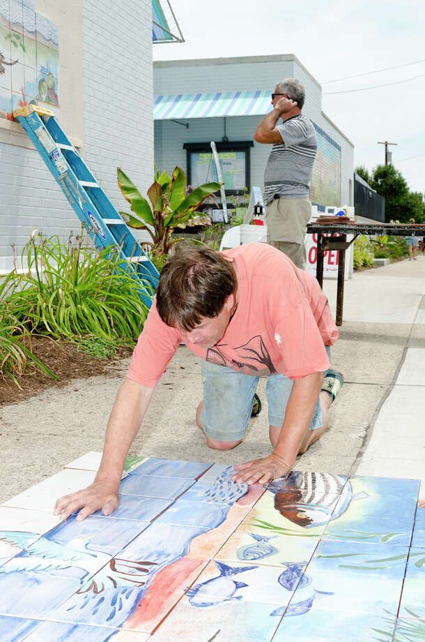 Artist Kim Salander positions tiles of which will be installed to create a 100 square foot mural at Calf Pasture Beach in Norwalk on Saturday, July 27, 2013. The tiles for the mural were created by artists Kim Salander and Georgette Wirth, of Wirth Salander Custom Tile. Photo: Amy Mortensen / Connecticut Post Freelance