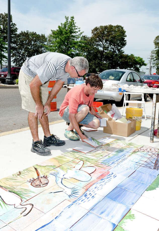 Nicolas Martinez and artist Kim Salander discuss plans to install a100 square foot mural at Calf Pasture Beach in Norwalk on Saturday, July 27, 2013. The tiles for the mural were created by artists Kim Salander and Georgette Wirth, of Wirth Salander Custom Tile. Photo: Amy Mortensen / Connecticut Post Freelance