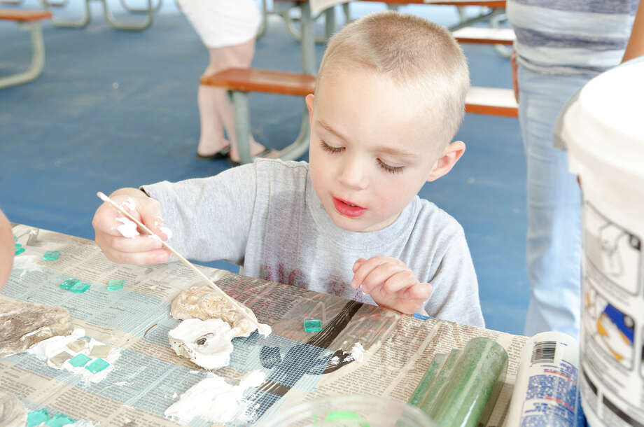 Michael Veltri, 4, of Norwalk, spreads tile cement on an oyster shell which will border the 100 square foot mural at Calf Pasture Beach in Norwalk on Saturday, July 27, 2013. The tiles for the mural were created by artists Kim Salander and Georgette Wirth, of Wirth Salander Custom Tile. Photo: Amy Mortensen / Connecticut Post Freelance
