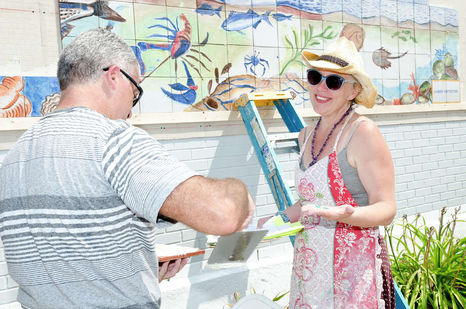 Nicolas Martinez spreads cement as artist Georgette Wirth discusses the border for a 100 square foot mural at Calf Pasture Beach in Norwalk on Saturday, July 27, 2013. The tiles for the mural were created by artists Kim Salander and Georgette Wirth, of Wirth Salander Custom Tile. Photo: Amy Mortensen / Connecticut Post Freelance