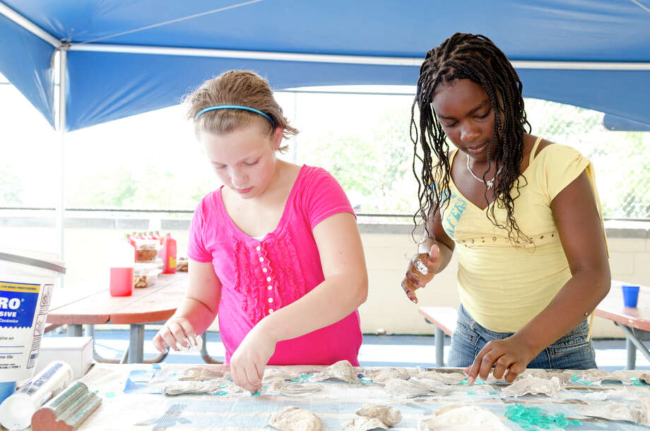 Morgan Veltri, 10, of Norwalk, and Erickah Tertulien, 10, of Norwalk, arrange glass tiles and oyster shells which will border the 100 square foot mural at Calf Pasture Beach in Norwalk on Saturday, July 27, 2013. The tiles for the mural were created by artists Kim Salander and Georgette Wirth, of Wirth Salander Custom Tile. Photo: Amy Mortensen / Connecticut Post Freelance