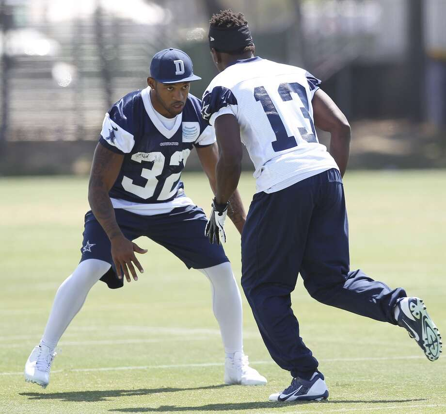 Cornerback Orlando Scandrick (32) keeps an eye on receiver Anthony Armstrong (13) during practice at the morning session of the 2013 Dallas Cowboys training camp on Saturday, July 27, 2013 in Oxnard. (Kin Man Hui/San Antonio Express-News) Photo: San Antonio Express-News