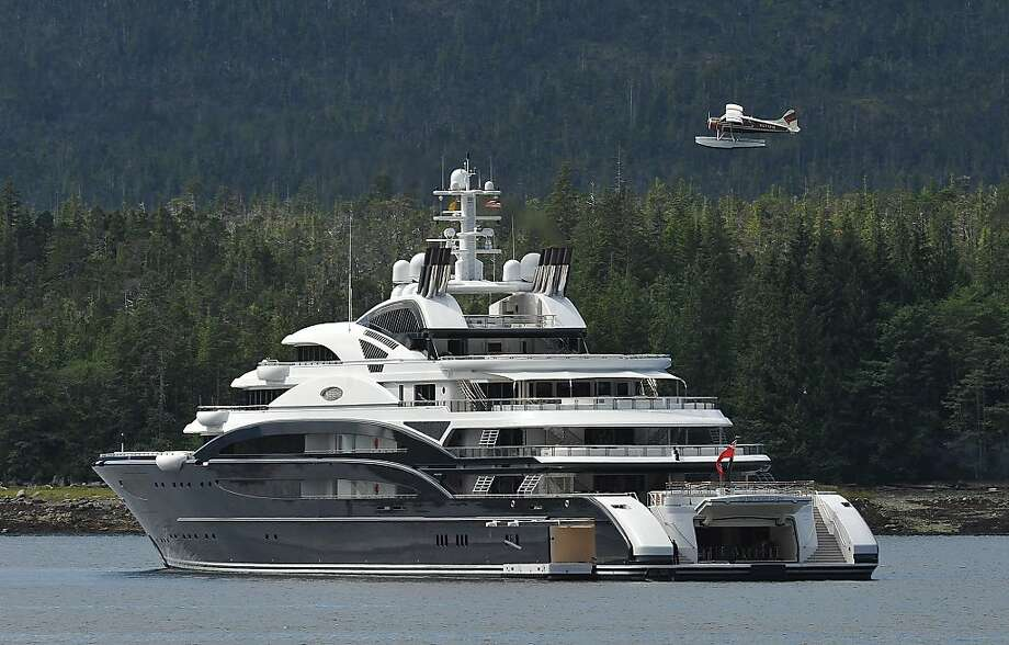 A float plane flies over the super yacht Serene during take off in Ketchikan, Alaska Friday morning. Work began on the 493-foot 3-inch yacht in 2007 by Italian shipbuilder Fincantieri. The ship has a crew of 52 and room for 24 guests. The seven deck vessel has landing capabilities for two helicopters and for a submarine and a sea water pool. (AP Photo/Ketchikan Daily News, Hall Anderson) Photo: Hall Anderson, Associated Press