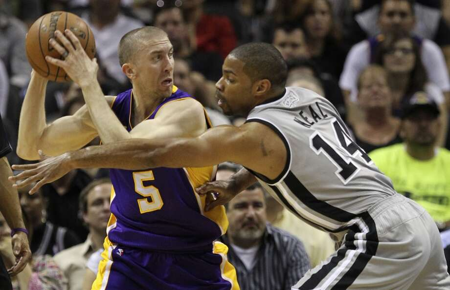 San Antonio Spurs' Gary Neal reaches over to try to steal the ball away from Los Angeles Lakers' Steve Blake during the first half of game 1 in the first round of the NBA Playoffs at the AT&T Center, Sunday, April 21, 2013. Photo: San Antonio Express-News