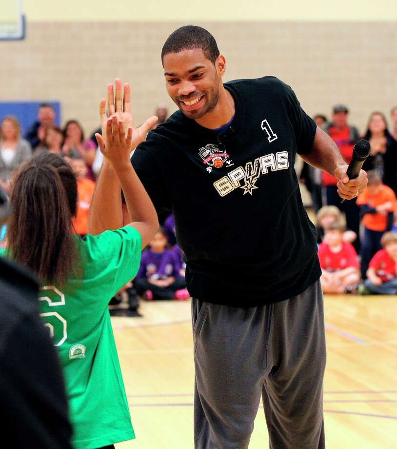 Spurs' guard Gary Neal (right) offers a high-five to Mikayla Whitby, 10, after a basketball drill competition during the Spurs Youth Basketball League Kids Clinic at the Walzem YMCA on Tuesday, Jan. 15, 2013. About a hundred kids came out to interact with Neal and Spurs Assistant Coach Brett Brown. The clinic stressed the importance of making good decisions and staying in school while also teaching the kids a few basketball fundamentals. Photo: Kin Man Hui, San Antonio Express-News / © 2012 San Antonio Express-News