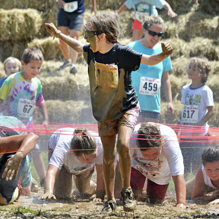 McKenzie Meredith, 10, center, of Edinburg during the 2K Family event at the 2013 Run the Ridge Mud Run hosted by Maple Ski Ridge in Mariaville, NY, on Saturday July 27, 2013. (John Carl D'Annibale / Times Union) Photo: John Carl D'Annibale / 00023252A