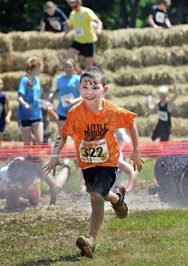 Lucas Raucci, 6, of Rotterdam clears an obstacle during the 2K Family run at the 2013 Run the Ridge Mud Run hosted by Maple Ski Ridge in Mariaville, NY, on Saturday July 27, 2013. (John Carl D'Annibale / Times Union) Photo: John Carl D'Annibale / 00023252A