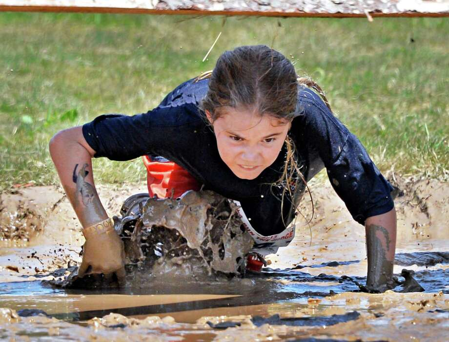 Tess Fitzmaurice, 10, of Greenville crawls through mud on her way to winning the 2K Family race at the 2013 Run the Ridge Mud Run hosted by Maple Ski Ridge in Mariaville, NY, on Saturday July 27, 2013. (John Carl D'Annibale / Times Union) Photo: John Carl D'Annibale / 00023252A