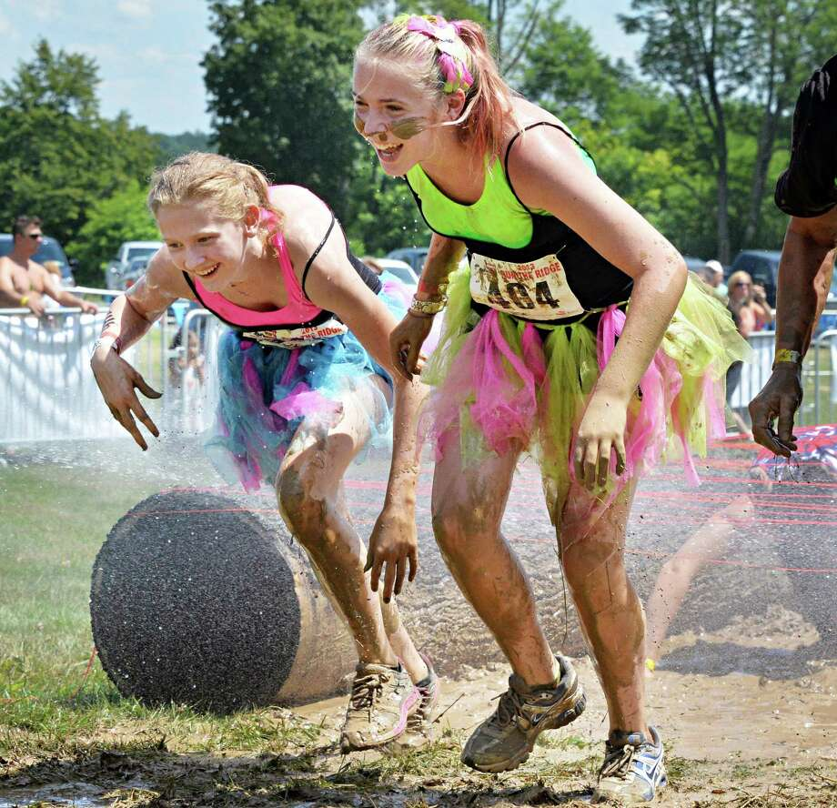 Wearing ballet tutus, Cassandra Ryan, 17, left, and Tierney Van Deusen, 14, both of Glenville, clear an obstacle during the 2K Family event at the 2013 Run the Ridge Mud Run hosted by Maple Ski Ridge in Mariaville, NY, on Saturday July 27, 2013. (John Carl D'Annibale / Times Union) Photo: John Carl D'Annibale / 00023252A