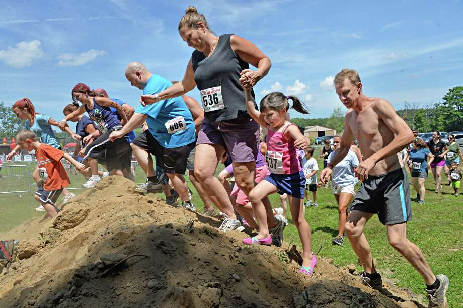 Competitors negotiate an obstacle during the 2K Family event at the 2013 Run the Ridge Mud Run hosted by Maple Ski Ridge in Mariaville, NY, on Saturday July 27, 2013. (John Carl D'Annibale / Times Union) Photo: John Carl D'Annibale / 00023252A