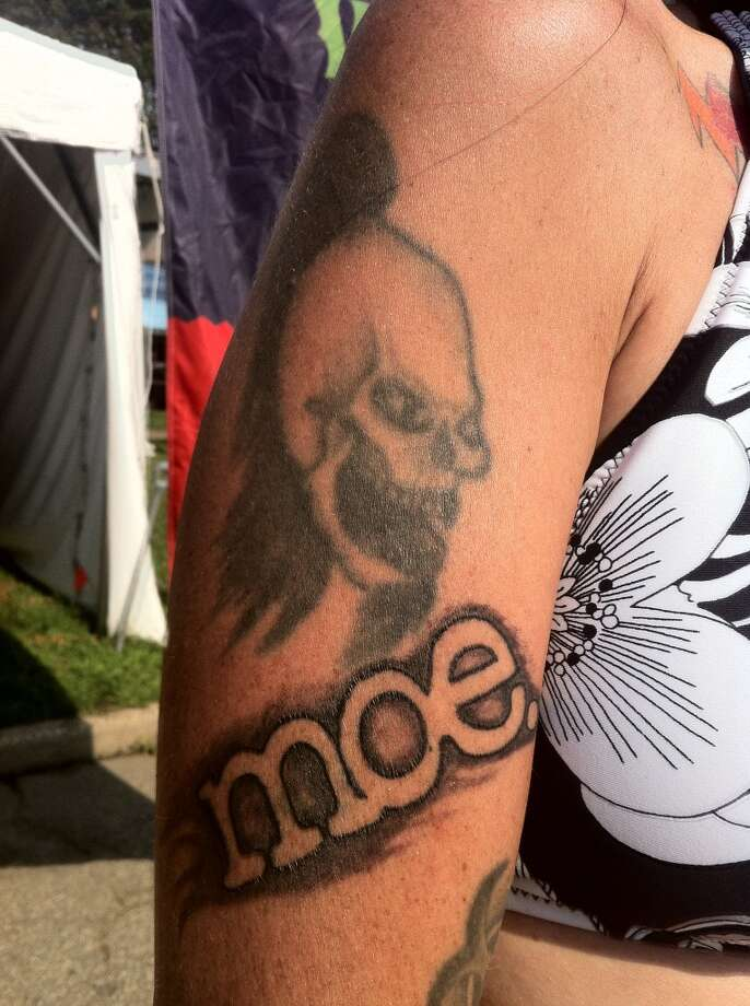 Georgie Galler, of Fairfield, shows off her tattoos of band logos -- Moe., String Cheese Incident, the Grateful Dead -- at Gathering of the Vibes on Saturday, July 28, 2013.