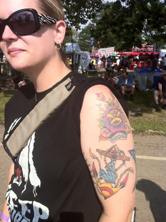 Stacy Taweny, wife of Mark Tawney, of Philadelphia shows off one of her 23 tattoos at the Gathering of the Vibes on Saturday, July 28, 2013.