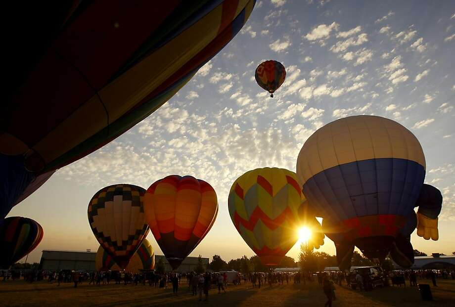 Balloons start to rise with the sun during the 2013 Casper Balloon Roundup's mass launch at the Central Wyoming Fairgrounds early Saturday, July 27, 2013 at the Central Wyoming Fairgrounds in Casper, Wyo. (AP Photo/Casper Star-Tribune, Dan Cepeda) Photo: Dan Cepeda, Associated Press