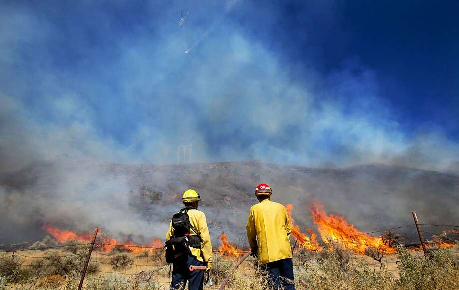 With a helicopter and water bucket flying overhead, firefighters wait for flames to reach them before spraying them down near the intersection of Clockum Pass Road and Tarpiscan Road  Saturday, July 27, 2013  near Malaga, Wash.  Nearly 1,200 fighters are battling a wildlfire that has grown to about 14 square miles near Goldendale, Wash. The fire along the top of Satus Pass is threatening about 180 fires, but none have been damaged.  (AP Photo/The Wenatchee World, Don Seabrook) Photo: Don Seabrook, Associated Press