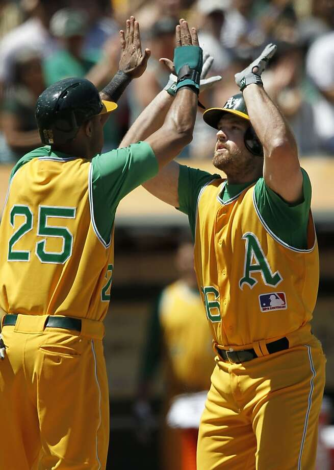Wearing the A's 1969 uniforms, Chris Young (left) thanks Derek Norris for getting them both home in the seventh. Photo: Michael Macor, San Francisco Chronicle