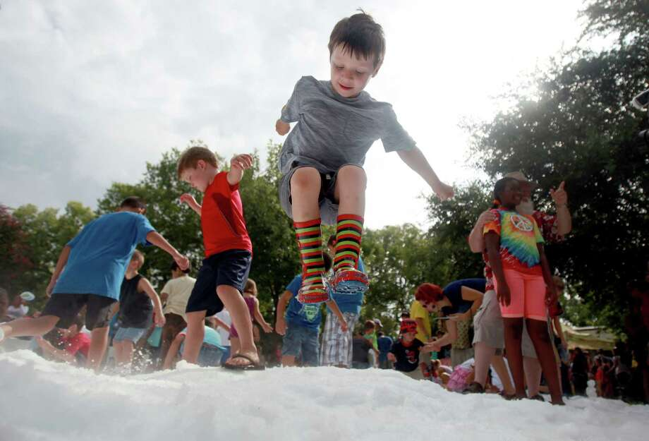 Henry Elbro, 4, in excitement jumps in the snow during TXU Energy Snow Day at the Houston Zoo on Saturday, July 27, 2013, in Houston. Photo: Mayra Beltran, Houston Chronicle / © 2013 Houston Chronicle