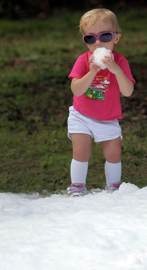 Annalise Rogers, 18 months-old, decides to taste the snowball she made during TXU Energy Snow Day at the Houston Zoo on Saturday, July 27, 2013, in Houston. Photo: Mayra Beltran, Houston Chronicle / © 2013 Houston Chronicle