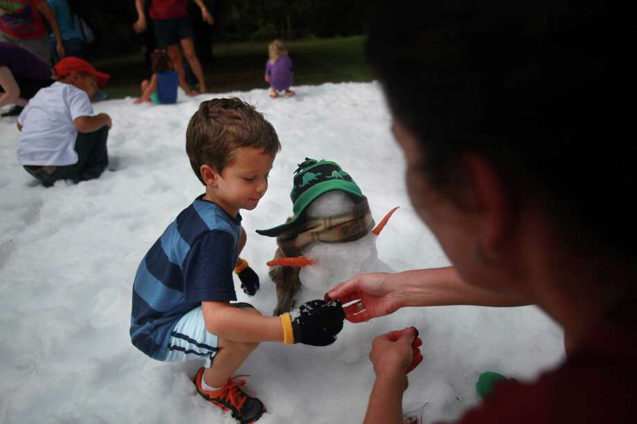 Dylan Perkins, 4, builds a snowman with the help of mother Susannah Perkins during TXU Energy Snow Day at the Houston Zoo on Saturday, July 27, 2013, in Houston. Photo: Mayra Beltran, Houston Chronicle / © 2013 Houston Chronicle
