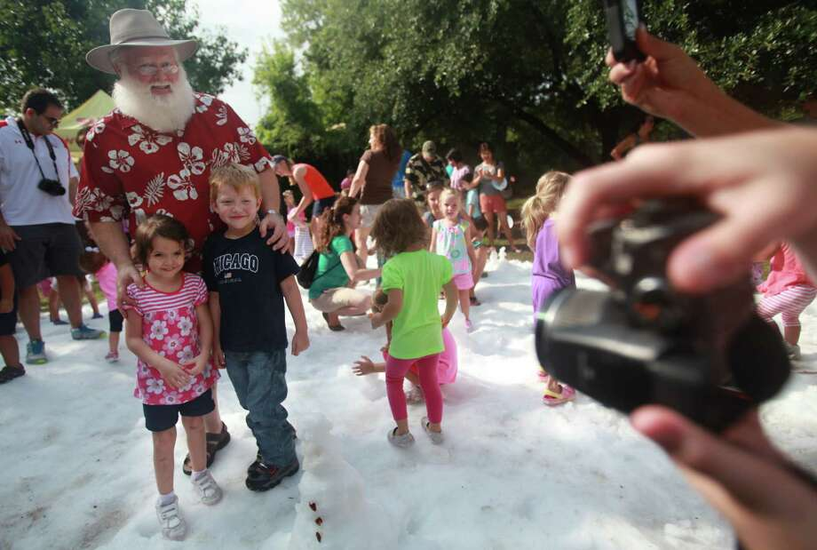 Paige Leal and Michael Scott wanted to take a photo with Santa during TXU Energy Snow Day at the Houston Zoo on Saturday, July 27, 2013, in Houston. Photo: Mayra Beltran, Houston Chronicle / © 2013 Houston Chronicle