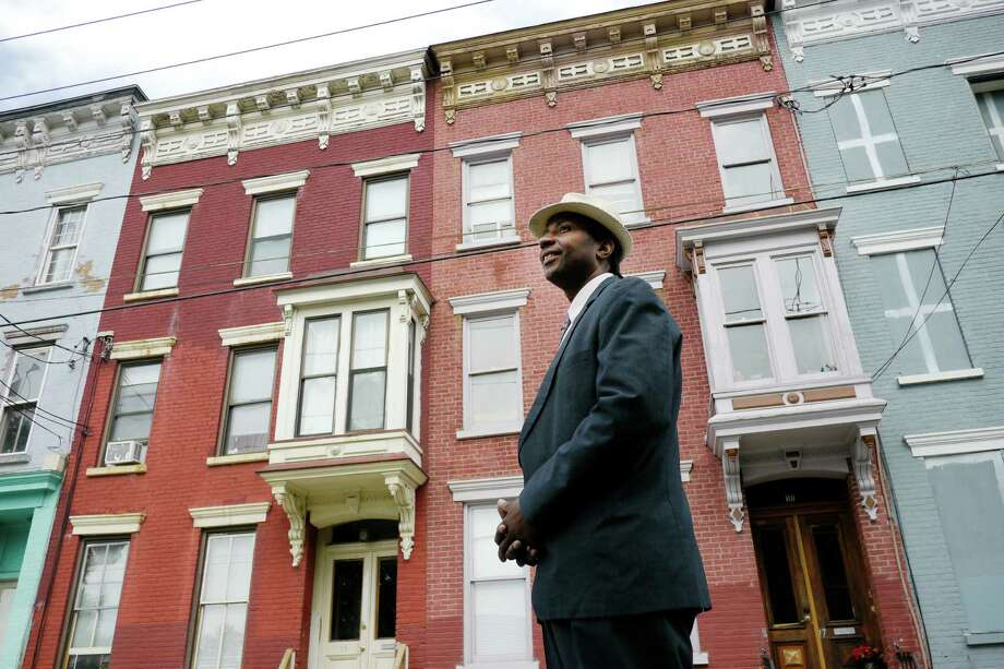 Mark Robinson stands on Lexington Avenue Thursday morning, July 25, 2013, in Albany, N.Y., in front of two apartment buildings he's rehabbed and is renting. (Paul Buckowski / Times Union) Photo: Paul Buckowski / 00023298A