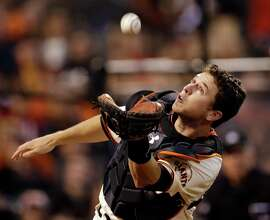 San Francisco Giants catcher Buster Posey makes a diving catch on a foul ball hit by St. Louis Cardinals' Matt Holliday during the fourth inning of Game 1 of baseball's National League championship series Sunday, Oct. 14, 2012, in San Francisco. (AP Photo/David J. Phillip)