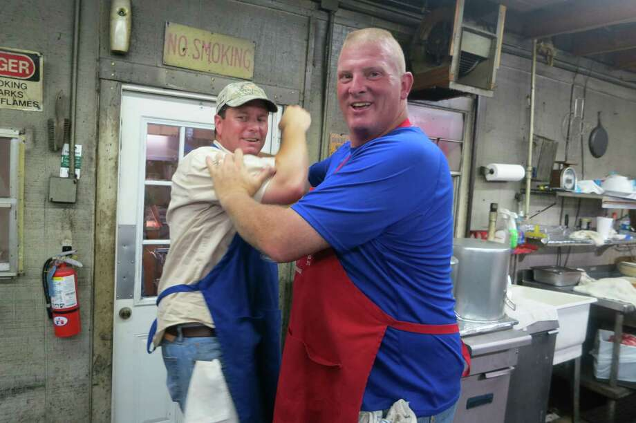 Don Crawford, a home builder, is the meat cutter, and Donnie Mordecai, a Waller deputy sheriff, is a cook at Leona General Store near Centerville, Texas. Photo: Joe Holley, Houston Chronicle / Houston Chronicle