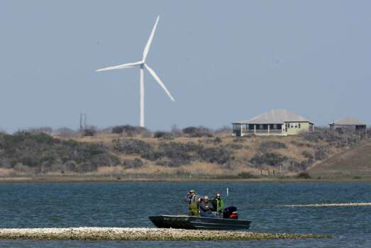 A fishing boat passes near a wind turbine near Ingleside, one of two in Kenedy County. Coastal wind farms draw complaints of blight by marring natural seaside views, in addition to disrupting birds' migratory paths. Research is being developed to deploy offshore wind turbines, which would eliminate those complaints - if they can be made cost-efficient. Photo: LM Otero, STF / AP