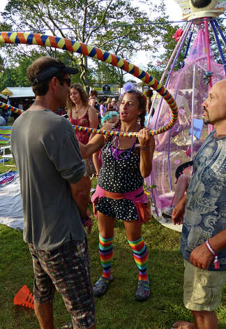 "Lauren Ardman, of New Paltz, NY, shakes a hoop over a ""customer"" as he goes through the Karma Wash, during the 18th Annual Gathering of the Vibes music festival at Seaside Park in Bridgeport, Conn. on Saturday July 27, 2013. Photo: Christian Abraham / Connecticut Post freelance"