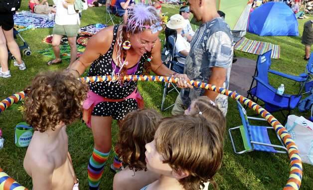 Lauren Ardman, of New Paltz, NY shakes a hoop over some children as they go through the Karma Wash, during the 18th Annual Gathering of the Vibes music festival at Seaside Park in Bridgeport, Conn. on Saturday July 27, 2013. Photo: Christian Abraham / Connecticut Post freelance