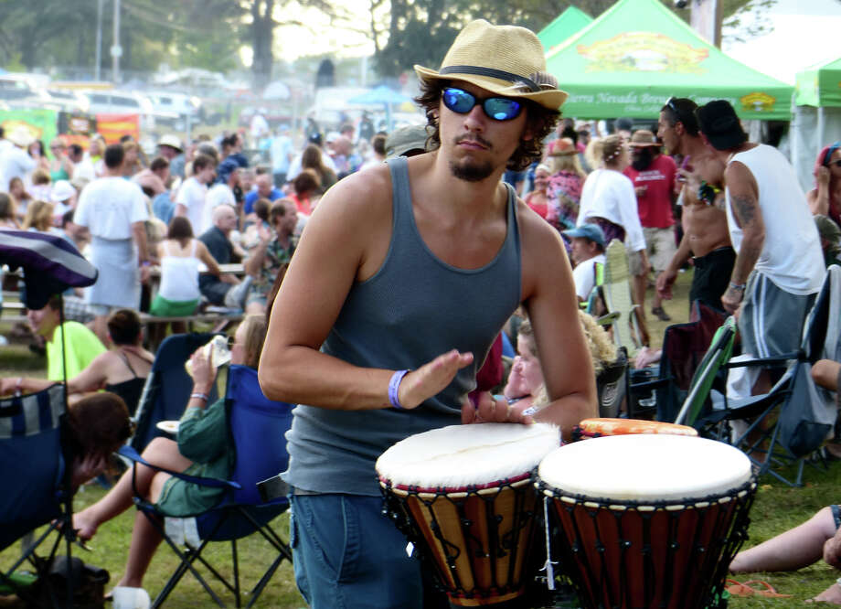 Jack Sheehan, of Trumbull, beats a conga drum set up for anyone passing by to play with during the 18th Annual Gathering of the Vibes music festival at Seaside Park in Bridgeport, Conn. on Saturday July 27, 2013. Photo: Christian Abraham / Connecticut Post freelance