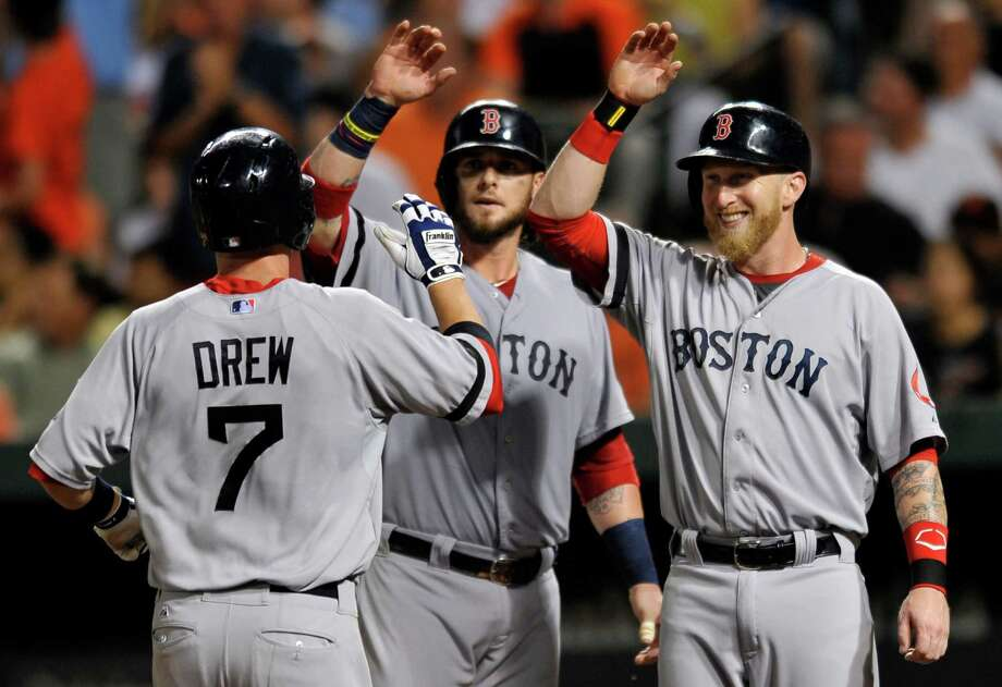 Boston Red Sox Stephen Drew, left, is congratulted by teammates Jarrod Saltalamacchia, center, and Mike Carp after hitting a three-run home run against the Baltimore Orioles in the fourth inning of a baseball game on Saturday, July 27, 2013, in Baltimore. (AP Photo/Gail Burton) ORG XMIT: MDGB104 Photo: GAIL BURTON / FR4095 AP