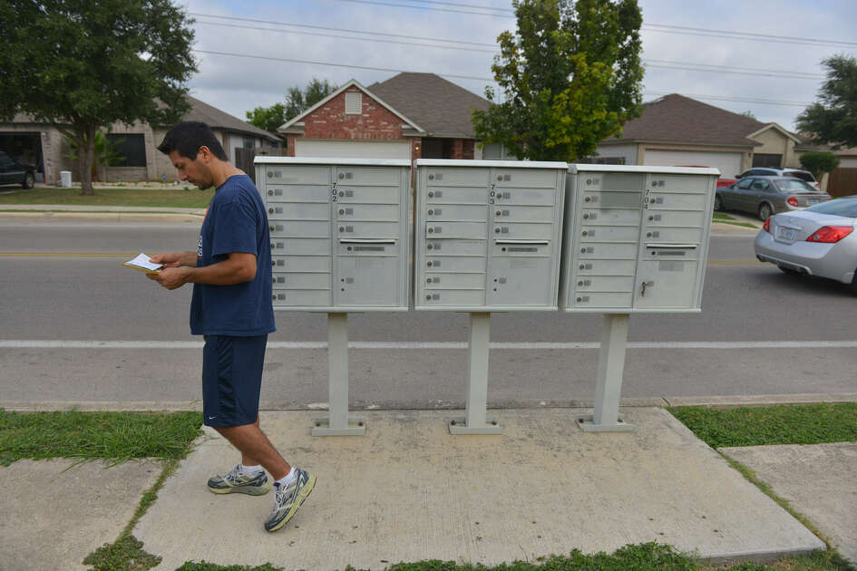 David Enrique picks up mail from a cluster of mailboxes near Thousand Oaks and Rowe Drive.