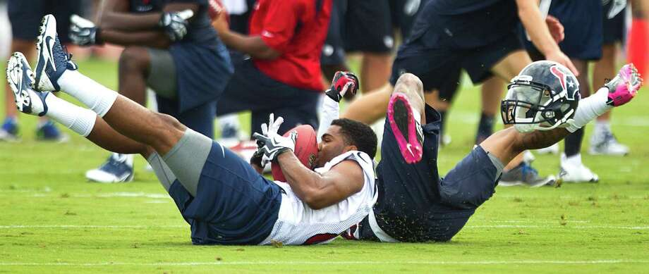 Houston Texans wide receiver Michael Smith, left, loses his helmet as he and cornerback Elbert Mack hit the ground during Texans training camp at the Methodist Training Center Saturday, July 27, 2013, in Houston. Photo: Brett Coomer, Staff / © 2013 Houston Chronicle