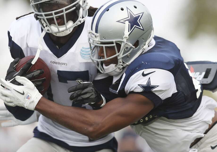 Safety Barry Church (right) tackles receiver Dwayne Harris (17) during the afternoon session of the 2013 Dallas Cowboys training camp on Saturday, July 27, 2013 in Oxnard. (Kin Man Hui/San Antonio Express-News) Photo: San Antonio Express-News