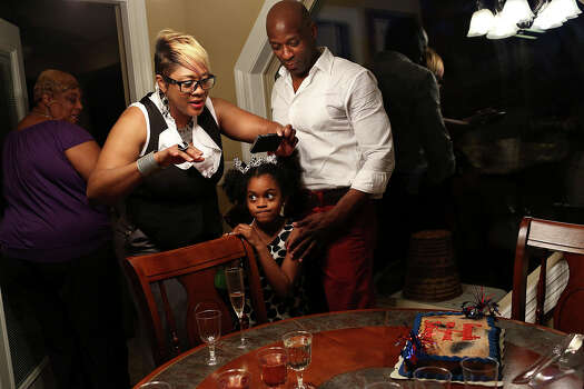 Chief Warrant Officer Christopher Royal stands with his cousin Shantye Jackson, left, and her daughter, Gabriel Ford, 6, as Jackson photographs his cake during a party for his retirement from the Army in his hometown of Eclectic, AL, on Saturday, July 13, 2013. Photo: Lisa Krantz, San Antonio Express-News / San Antonio Express-News