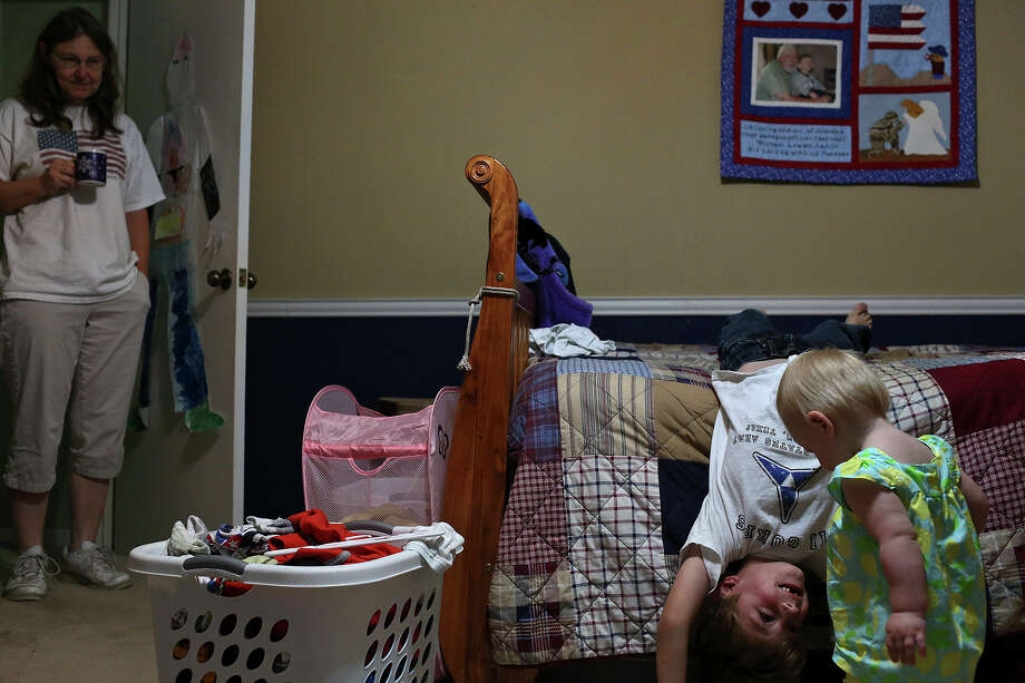 Joleen Cahill watches as her grandchildren, Brody, 6, and Kate, 1, play in Brody's room where a quilt, right, memorializing his grandfather, Mike Cahill, hangs above his bed in Kerrville on July 4, 2013. Photo: Lisa Krantz, San Antonio Express-News / San Antonio Express-News