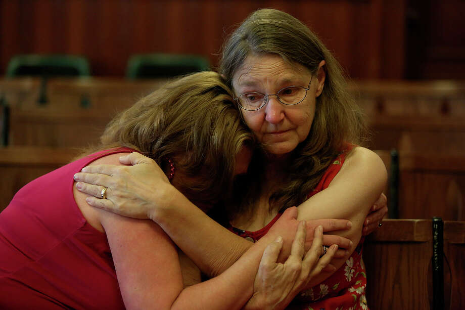 Misty Kirk, left, is embraced by Joleen Cahill, right, during Cahill's retirement party at the Milam County Courthouse in Cameron. Cahill is retiring after 13 years as a legal secretary to attend the trial of Army Major Nidal Malik Hasan at Ft. Hood, get the Ft. Hood November 5, 2009 Memorial built and spend more time with her family. Photo: Lisa Krantz, San Antonio Express-News / San Antonio Express-News