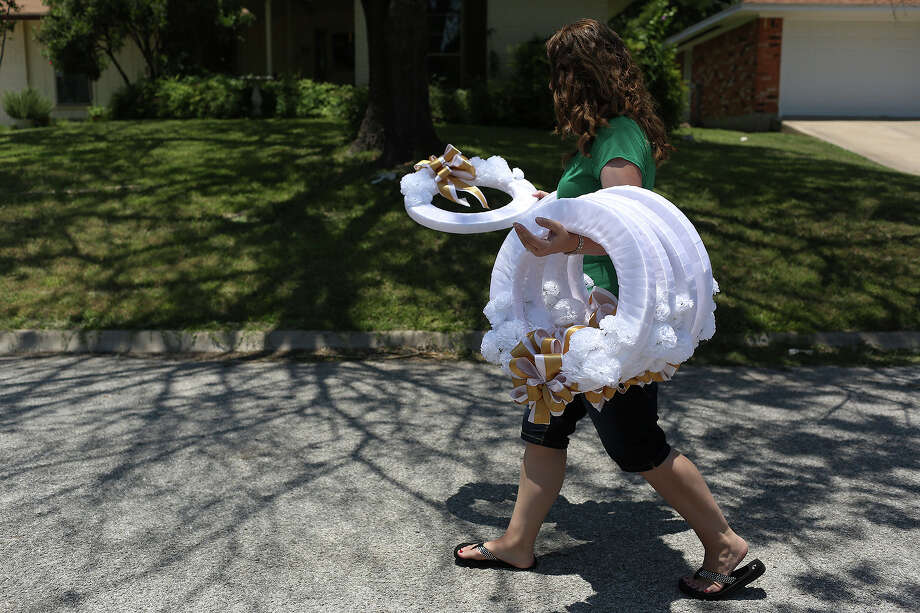 Keely Cahill Vanacker carries wreaths her family had made for the victims of the Ft. Hood shooting rampage that also took the life of her father, Mike Cahill, at her home in Kerrville on July 5, 2013. The Cahill family began memorializing the victims and survivors and also the first responders, SRP, medical and law enforcement personnel on the fence surround the SRP where the shooting occurred. As the trial approaches, they had special wreaths made for the victims, first responders, SRP, medical and law enforcement and hand made ribbons adorned with stars for the 32 survivors. Photo: Lisa Krantz, San Antonio Express-News / San Antonio Express-News