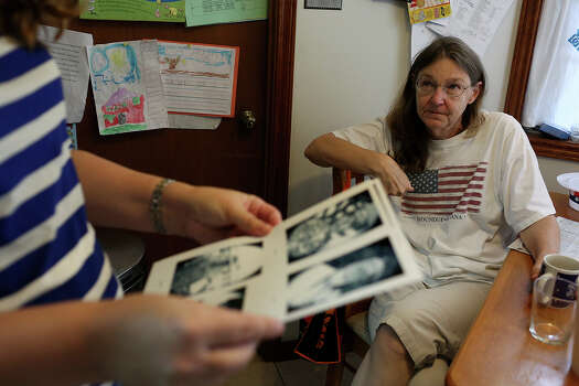 Keely Cahill Vanacker shows her mom, Joleen Cahill, the pictures she is printing to put on wreaths they had made for the 13 victims, including her father and Joleen's husband, of the Ft. Hood shooting at her home in Kerrville on July 4, 2013. Photo: Lisa Krantz, San Antonio Express-News / San Antonio Express-News