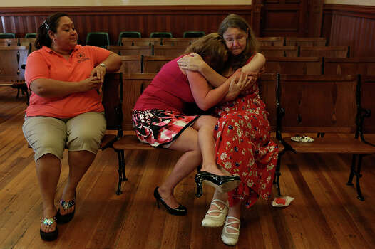 Joleen Cahill embraces an emotional Misty Kirk next to Margot Contreras, left, during Cahill's retirement party at the Milam County Courthouse in Cameron on Tuesday, July 23, 2013. Cahill retired so she could attend the entire trial of Army Major Nidal Malik Hasan at Ft. Hood, the man who is being tried for killing her husband and 12 others, to get the Ft. Hood November 5, 2009 Memorial built and to spend more time with her family. Photo: Lisa Krantz, San Antonio Express-News / San Antonio Express-News