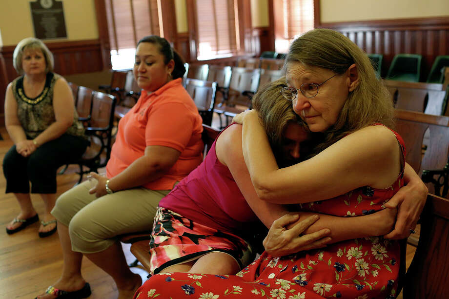 Joleen Cahill embraces an emotional Misty Kirk during Cahill's retirement party at the Milam County Courthouse in Cameron on Tuesday, July 23, 2013. Cahill retired so she could attend the entire trial of Army Major Nidal Malik Hasan at Ft. Hood, the man who is being tried for killing her husband and 12 others, and to get the Ft. Hood November 5, 2009 Memorial built and spend more time with her family. Photo: Lisa Krantz, San Antonio Express-News / San Antonio Express-News