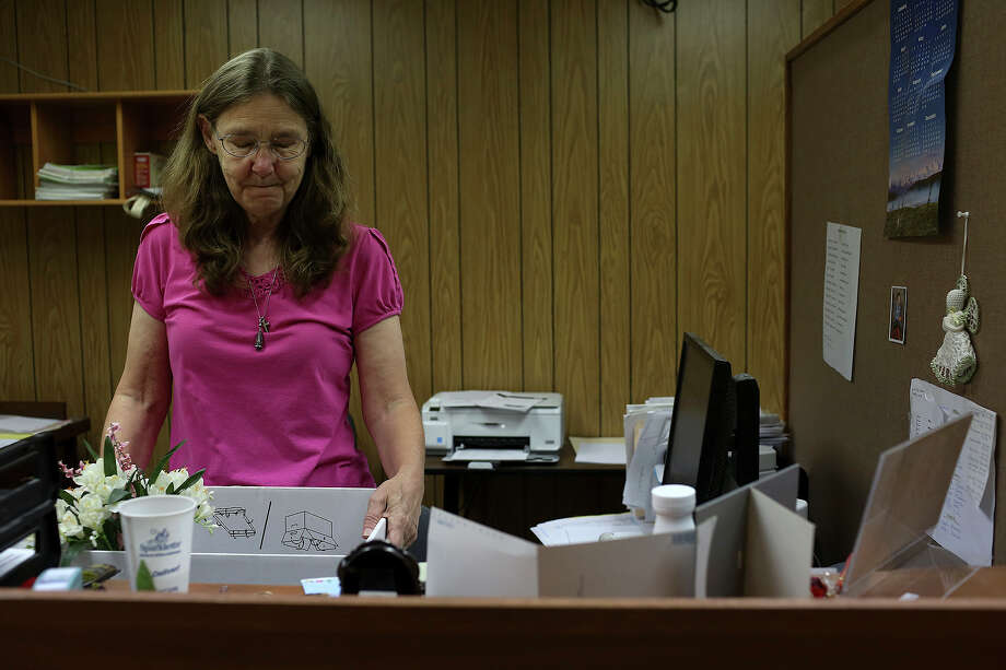 Joleen Cahill holds back tears after looking at a photograph of her husband, Mike Cahill, on her desk as she packs a box of personal items on her set retirement day at the Milam County District Attorney's office after working 13 years there as a legal secretary in Cameron on July 16, 2013. She set her retirement date as the same day of her husband's birthday, July 16, but had to work a few extra days to tie up loose ends. Photo: Lisa Krantz, San Antonio Express-News / San Antonio Express-News